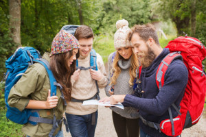 adventure, travel, tourism, hike and people concept - group of smiling friends with backpacks and map outdoors