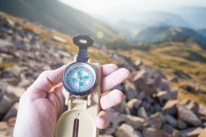 Picture of tourist's hand using a compass. At the background a beautiful valley with tops of mountain. Switzerland.