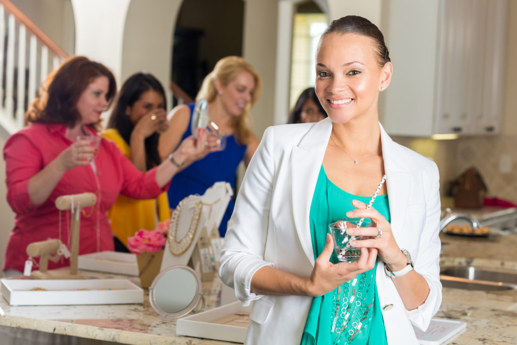 Mid adult African American professional woman is smiling while looking at the camera. She is holding a beverage while attending a direct sales party to purchase jewelry. Women are shopping in jewelry display set up in home. Customers are trying on products and placing orders.